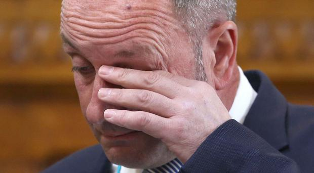 Mark Tipper, whose brother was one of the soldiers killed in the IRA bombing in Hyde Park in 1982, wipes his eye after speaking at the launch of a campaign to raise funds to bring a case against John Downey, at the Palace of Westminster in London