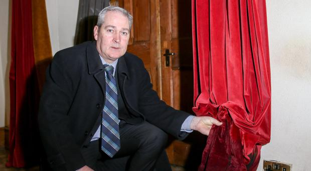 David Gantley, diocesan property administrator, with curtains damaged during a previous attack on St Patrick's Church in January
