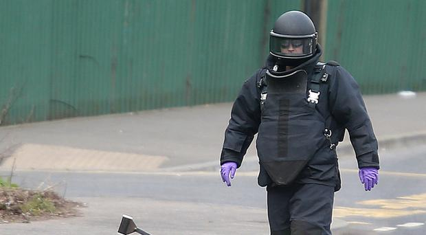 A bomb disposal officer with a dissident republican under-car booby-trap device during a security alert in west Belfast in March 2014
