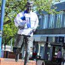 The Bertie Peacock statue draped with a Coleraine FC shirt and scarves in the centre of the town