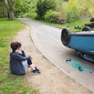 Charity worker Katy Skelton sits distraught beside her vandalised Mini at Cave Hill park, Belfast