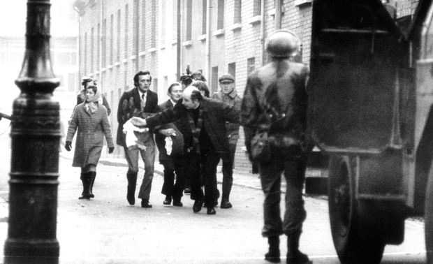 A young Fr Edward Daly carries a blood-soaked hankie as he leads a group of men trying desperately to carry John 'Jackie' Duddy to safety. Duddy (17) was the first fatality of Bloody Sunday after being shot from behind by paratroopers