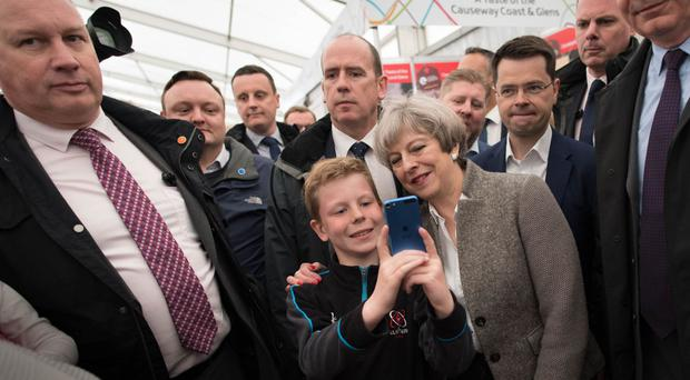 Prime Minister Theresa May poses for a selfie while visiting the Balmoral Show near Lisburn