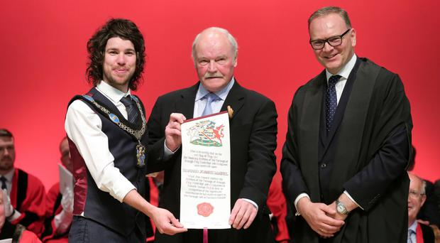 Ronnie McFall receives his scroll from Lord Mayor of Armagh City, Banbridge and Craigavon Borough Garath Keating and council chief executive Roger Wilson