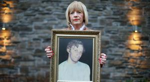 Karen Armstrong holds a photograph of her brother John McConville, who was killed in the Kingsmill attack