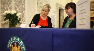 Sinn Fein's Michelle O'Neill and Mary Ellen Campbell sign the book of condolence for the victims of the Manchester bombing at Belfast City Hall.