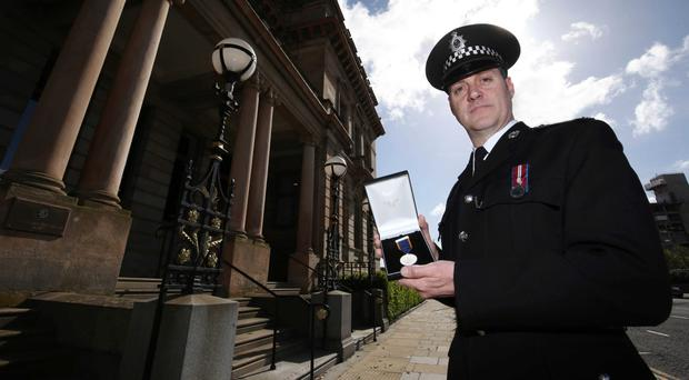 Belfast Harbour Police Constable Scott Harkins with his gallantry medal