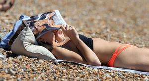 A woman enjoys the warm weather on the beach in Brighton, East Sussex