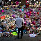 A bystander views the mass of floral tributes to the victims of the Manchester bombing at St Ann's Square in the city