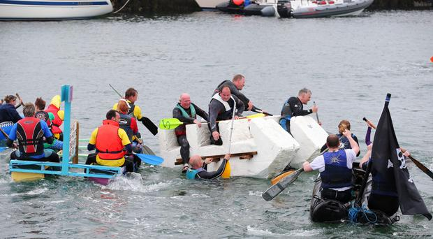 Competitors take part in the annual Portrush Raft Race at the harbour in aid of the RNLI