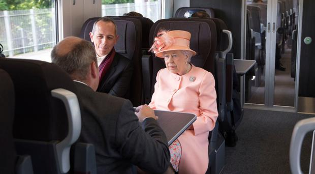 The Queen sits next to Isambard Thomas, great-great-great grandson of Isambard Kingdom Brunel, on a train travelling from Slough to Paddington Station to mark the 175th anniversary of the first train journey by a British monarch