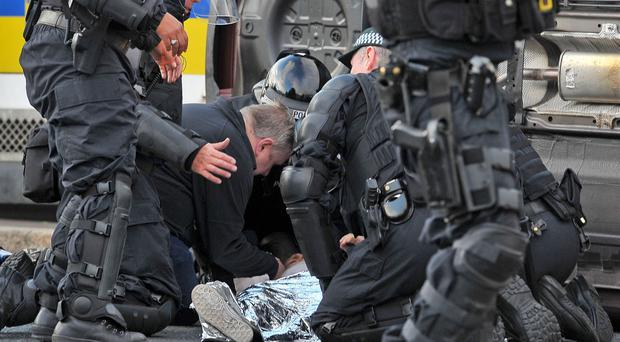 Police officers treat Phoebe Clawson after she was struck by a car driven by Aughey in Ardoyne in July 2015