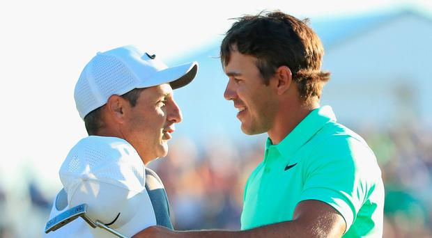 Brooks Koepka is congratulated by caddie Ricky Elliot after winning the 2017 US Open