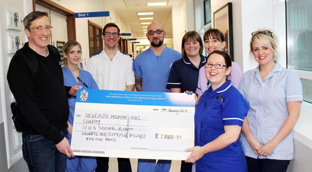 Tommy McManus (left) hands over a cheque for £7,865 to staff of the Freeman Hospital in Newcastle Upon Tyne