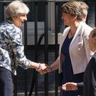Prime Minister Theresa May shakes the hand of DUP leader Arlene Foster outside 10 Downing Street
