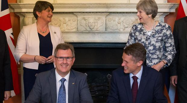 Theresa May stands with DUP leader Arlene Foster (left) as DUP MP Sir Jeffrey Donaldson (second right) and Parliamentary Secretary to the Treasury Gavin Williamson agreed a deal to support the minority Conservative government