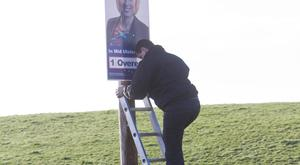 An election poster being put up before the election