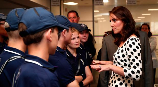 The Duchess of Cambridge chats to ball boys and girls on the first day of Wimbledon