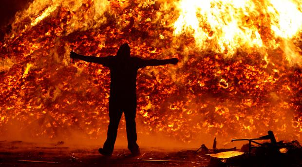 A young man watches a bonfire in Shankill Road in Belfast last year, when fire crews attended 33 incidents