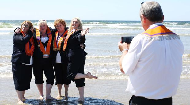Members of the Orange Order cool off with a paddle in the sea