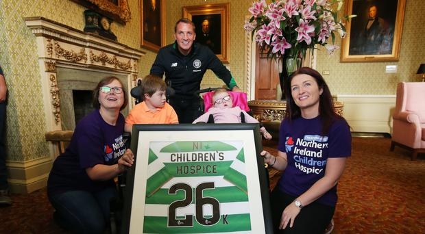 Brendan Rodgers, who is a NI Hospice ambassador, presents a signed shirt to the NI Children's Hospice. He is pictured with Moral Mullan (left), her son Luke, Michelle Neill and Aimee