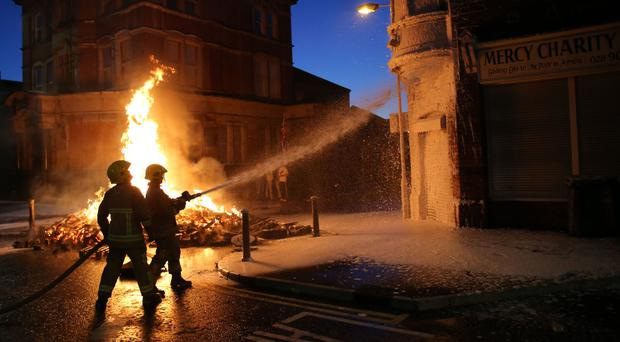 Firefighters douse nearby buildings as a bonfire is lit.