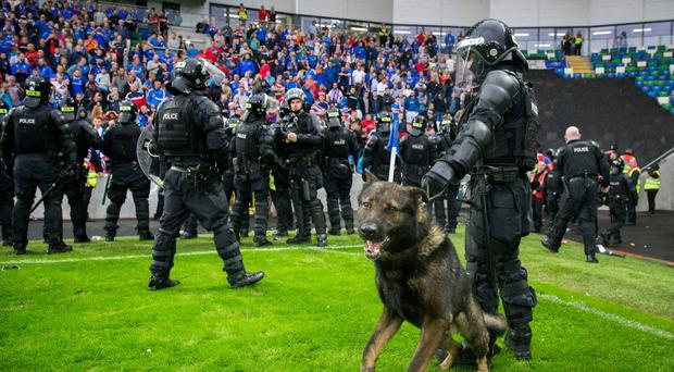 Police in riot gear stand on the pitch in front of Linfield fans after the match. Photo: Liam McBurney/PA