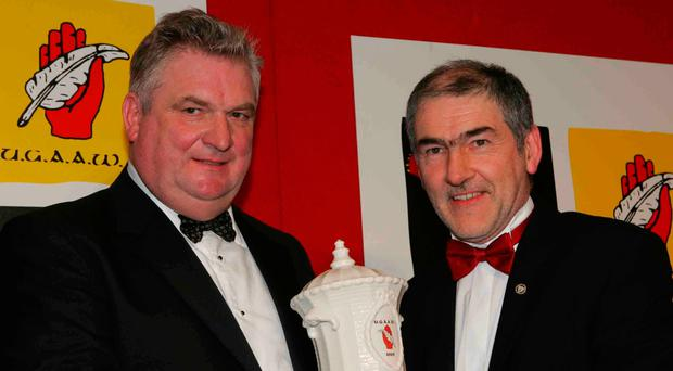Seamus Horisk (left) presenting Tyrone manager Mickey Harte with an award