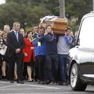 The coffin of Seamus Horisk is carried into St Matthew's chapel in Garvaghey, Ballygawley. Legendary GAA footballer Peter Canavan is pictured at the back of the cortege