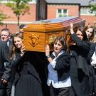 The coffin of Billy McConville is taken from St Paul's Parish Church, Belfast, following his funeral yesterday