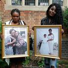 Relatives Miriam and Mary hold pictures of the late Mary Mendy (right) and Khadija Saye at a memorial service for five of the victims