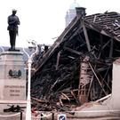 The Cenotaph at Enniskillen with the devastated community centre in the background. the killing of all