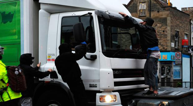 Two protesters jump on a lorry as it attempts to drive through makeshift road blocks at a protest in Kingsland Road in east London yesterday