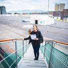 Claire McNeilly on the cruise ship gangplank with a not-so-enticing first sight of Belfast in the background