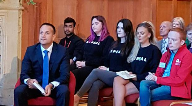 Three female students in black 'Repeal' sweaters sat directly behind the taoiseach during his visit to Queen's University