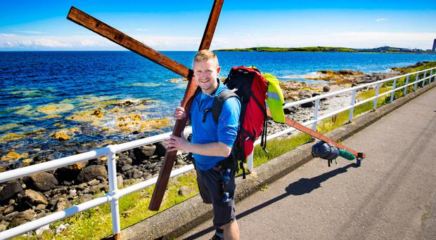 Glen Connor on his trek carrying a cross along the coast road