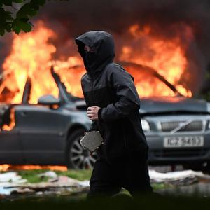 A hooded rioter armed with a rock taking part in one of the riots