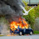 A car is left burning after it was set alight during a riot