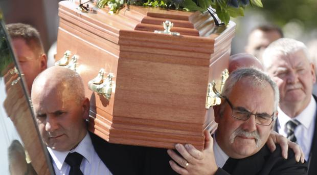Friends and family carry the coffin of James Moore following his funeral service