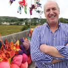 Farmer John Sheridan stands beside an art installation called Soften the Border