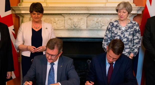 Arlene Foster and Theresa May look on as DUP MP Jeffrey Donaldson signs paperwork with Parliamentary Secretary to the Treasury Gavin Williamson inside 10 Downing Street