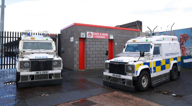 Police officers carry out searches at Crusaders Football club in north Belfast yesterday