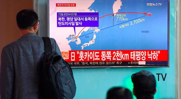 A man at a railway station in Seoul watches a screen showing a graphic of a North Korean missile launch yesterday