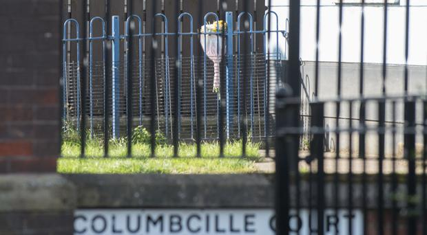 Flowers are left close to the McLaughlin family home at Columbcille Court in Derry where three-year-old Kayden was found dead on Sunday morning