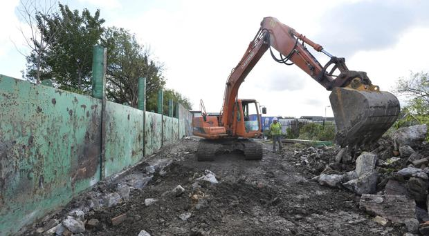Work has started to remove a three-metre high security wall that divides Springfield Road and Springhill Avenue