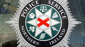 A man has robbed a business in west Belfast whilst threatening staff with a hammer.
