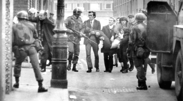 Father Edward Daly shepherds civilians as they carry a wounded man on Bloody Sunday