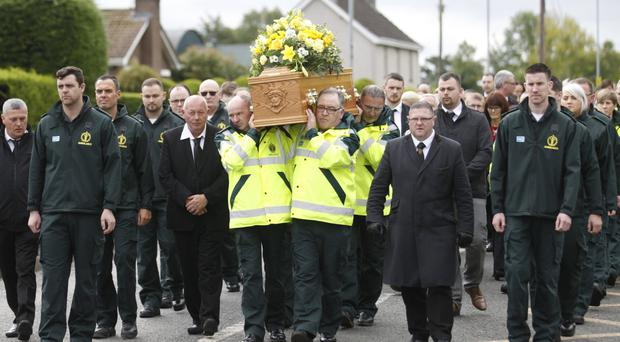 Paramedics carry the coffin of Michael Hughes during his funeral in Crumlin yesterday