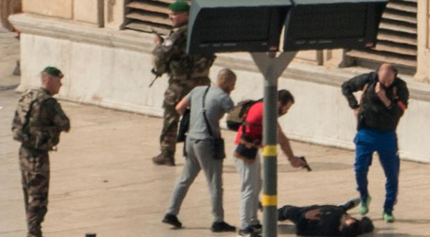 Police point a gun at suspect on the ground while soldiers secure the area after yesterday's stabbings in Marseille