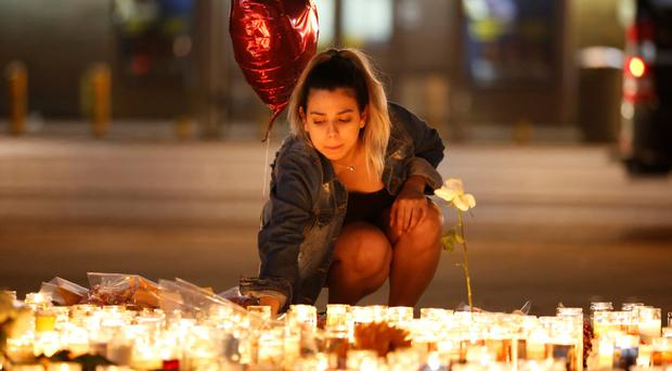 A woman lights candles at a vigil on the Las Vegas Strip